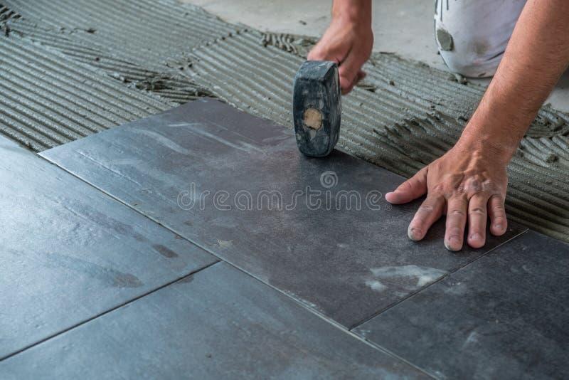 Arbetare som förlägger keramiska golvtegelplattor på självhäftande yttersida fotografering för bildbyråer