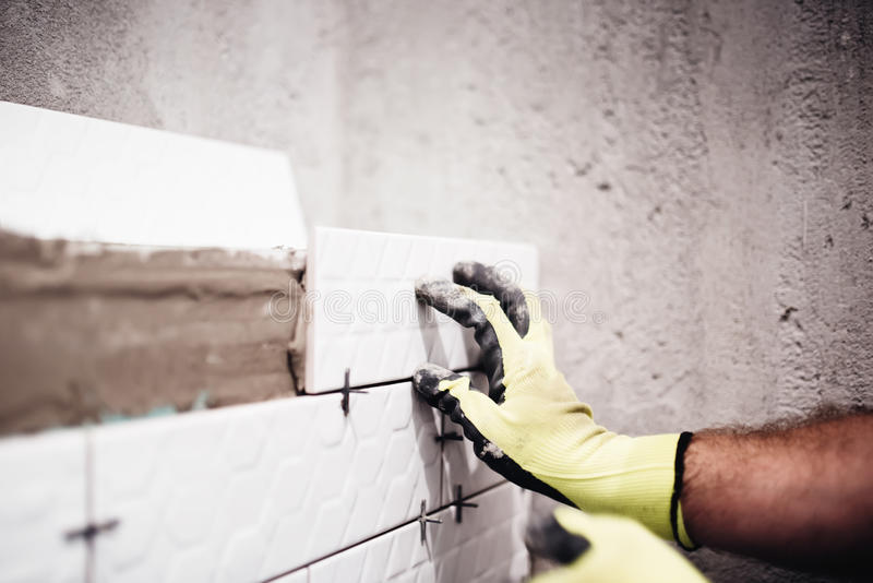 Arbetare som förlägger små keramiska tegelplattor med den plast- avståndsmätaren på badrumväggar fotografering för bildbyråer