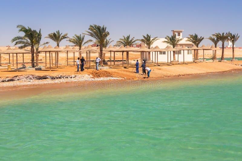 Arbetare som fixar kustlinjen av den tropiska semesterorten nära Hurghada royaltyfri fotografi