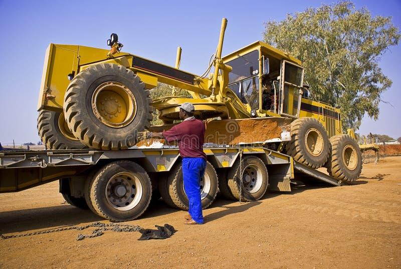 Arbetare som flyttar en väghyvel - Caterpillar 140H Transpo royaltyfri bild