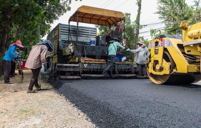 Arbetare som fungerar den industriella asfaltpavermaskinen under huvudvägkonstruktion royaltyfri fotografi