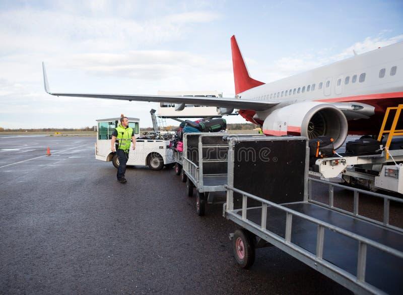 Arbetare som går med bagagesläp på landningsbana fotografering för bildbyråer