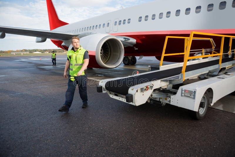 Arbetare som går med transportörlastbilen med flygplanet på landningsbana arkivfoton