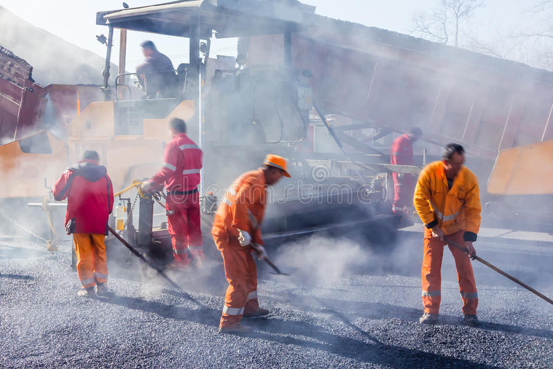 Arbetare som gör asfalt med skyfflar på vägen royaltyfria foton