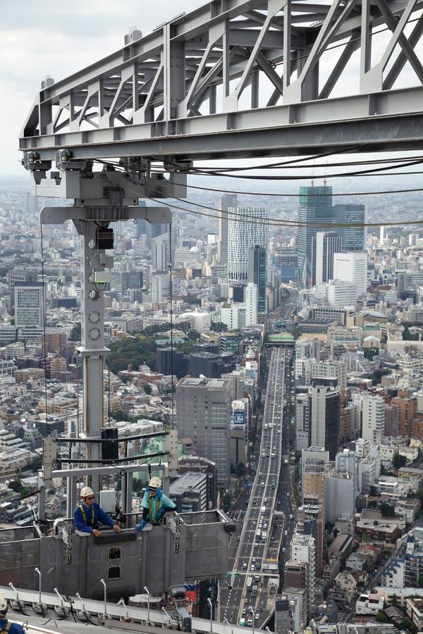 Arbetare som g?r ren f?nstret av den h?ga byggnaden i tokyo Japan fotografering för bildbyråer