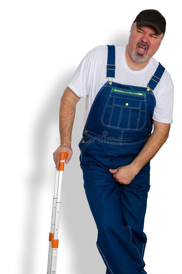 Arbetare som griper hans ljumske i obehag arkivfoto
