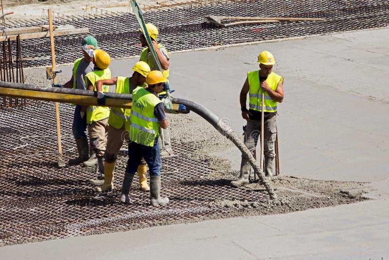 Arbetare som häller den konkreta konstruktionsplatsen arkivfoto