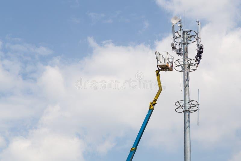 Arbetare som installerar antennen på högväxt telekommunikationtorn arkivbild
