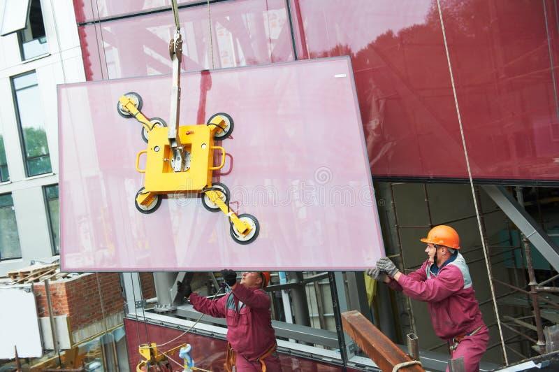 Arbetare som installerar det glass fönstret på byggnad arkivfoton