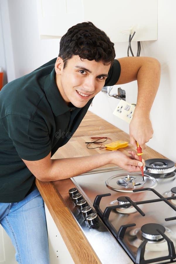 Arbetare som installerar gasspisen i nytt kök fotografering för bildbyråer