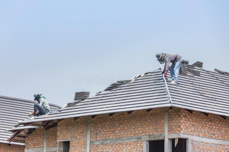 Arbetare som installerar konkreta tegelplattor på taket royaltyfria foton