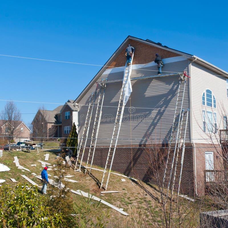 Arbetare som installerar plast- sidingpaneler på hus för två berättelse. arkivbilder