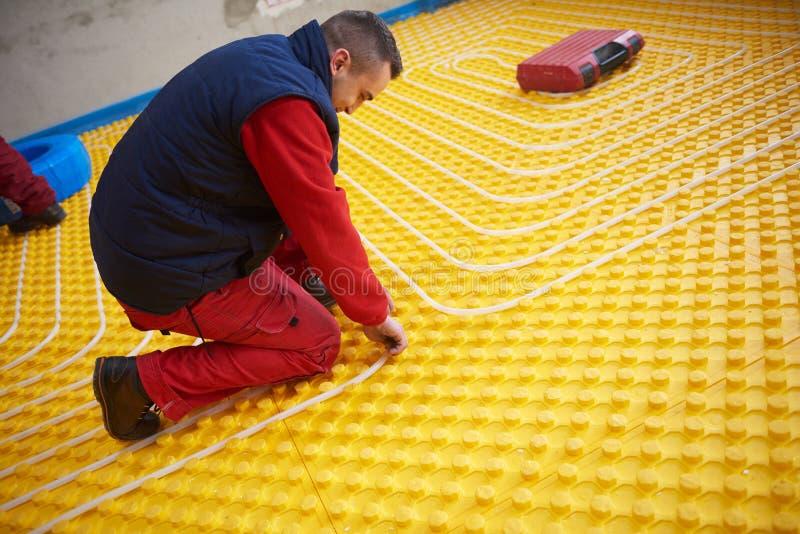Arbetare som installerar systemet för underfloor uppvärmning royaltyfria foton