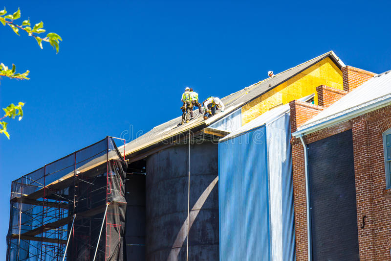 Arbetare som installerar taklägga material över tappninglagringsbehållare royaltyfria bilder