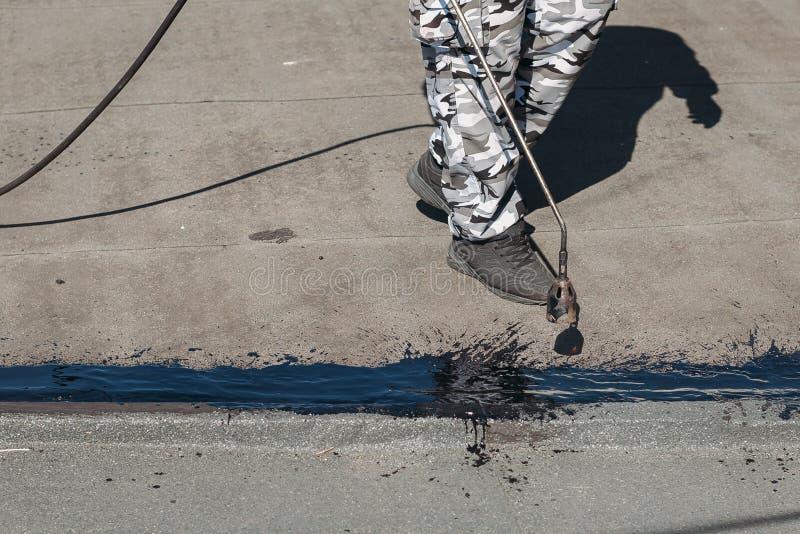 Arbetare som installerar tjärafolie på taket av byggnad Vattentätt system, genom att tända eld på för gas och för brand Takrepara royaltyfri fotografi