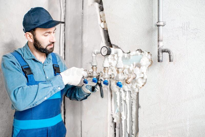 Arbetare som installerar vattenuppvärmningsystemet arkivfoton