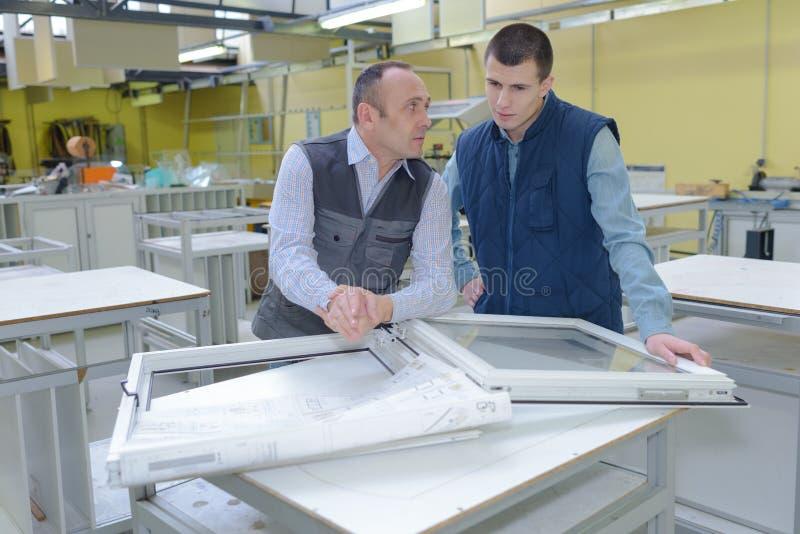 Arbetare som klipper fönsterprofiler i fabrik arkivbilder