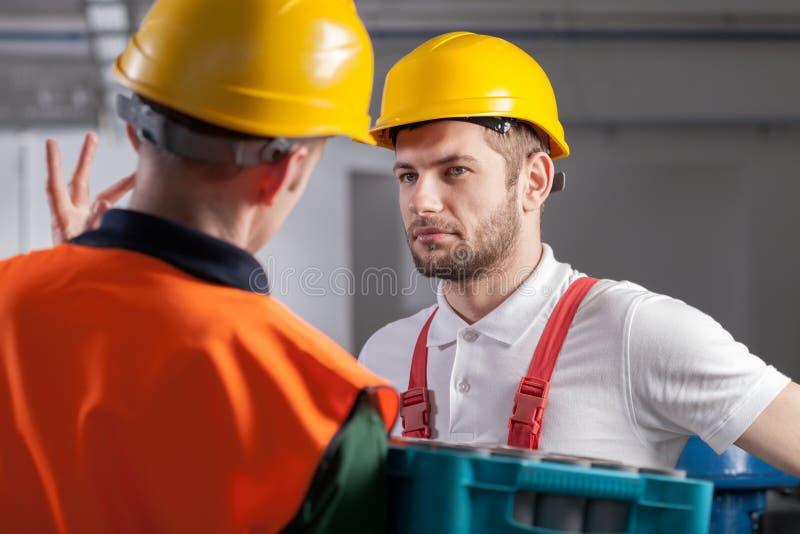 Arbetare som konsulterar med chefen i fabrik royaltyfri bild