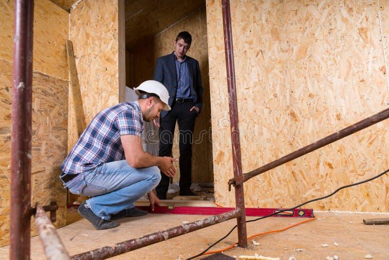 Arbetare som kontrollerar dörrramnivån i nytt hem fotografering för bildbyråer