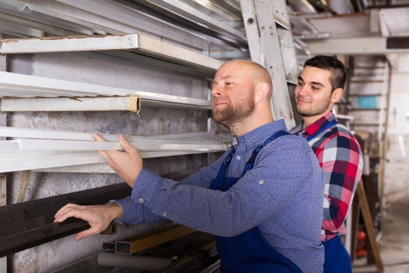 Arbetare som kontrollerar fönsterramar royaltyfria bilder