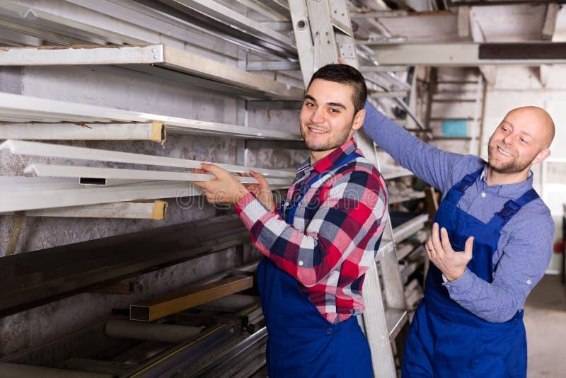 Arbetare som kontrollerar fönsterramar royaltyfri foto