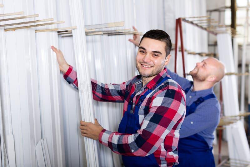 Arbetare som kontrollerar fönsterramar royaltyfri bild