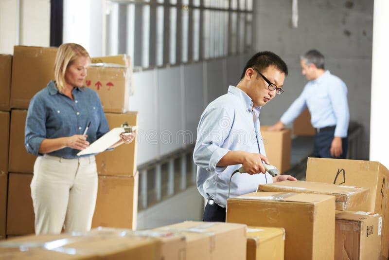 Arbetare som kontrollerar gods på bältet i fördelningslager arkivfoton