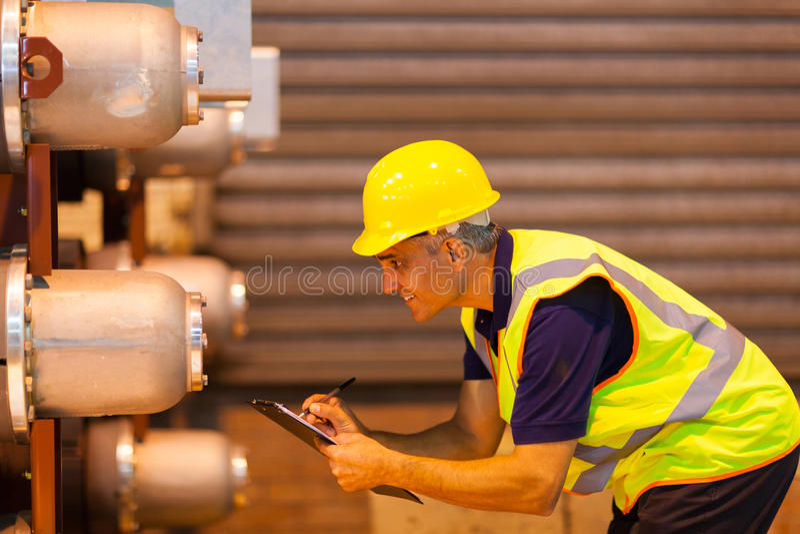 Arbetare som kontrollerar maskineri fotografering för bildbyråer