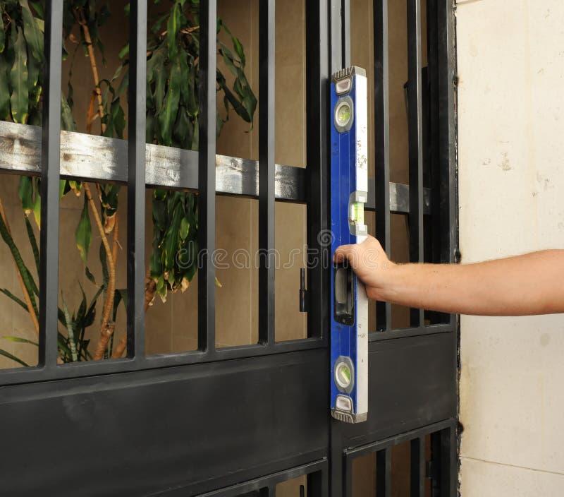 Arbetare som kontrollerar med det jämna hjälpmedlet den korrekta placeringen av en metallingångsdörr arkivfoton