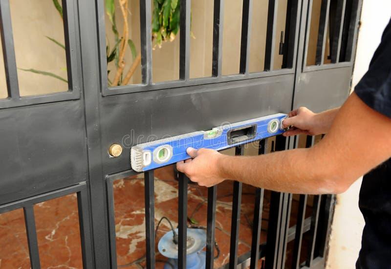 Arbetare som kontrollerar med det jämna hjälpmedlet den korrekta placeringen av en metallingångsdörr arkivbild