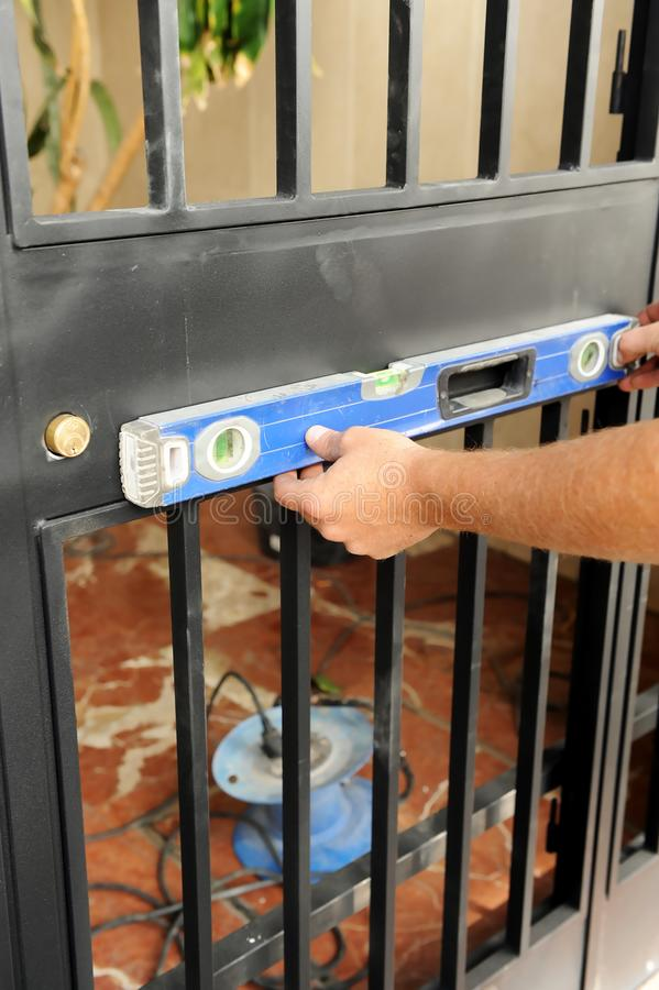 Arbetare som kontrollerar med det jämna hjälpmedlet den korrekta placeringen av en metallingångsdörr arkivfoto