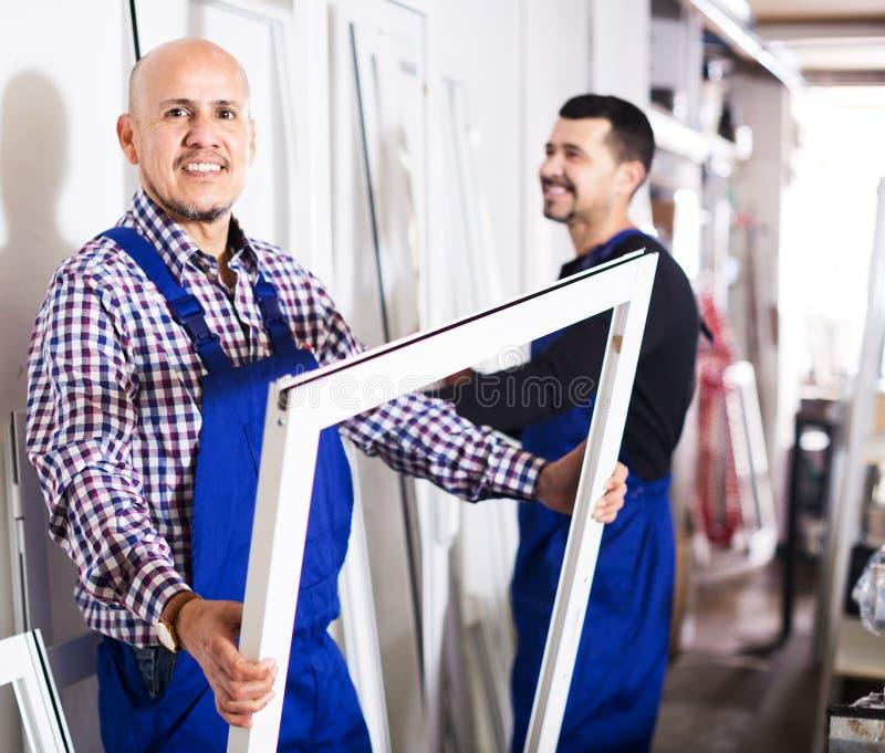 Arbetare som kontrollerar PVC-tillverkningsefterbehandling royaltyfri fotografi