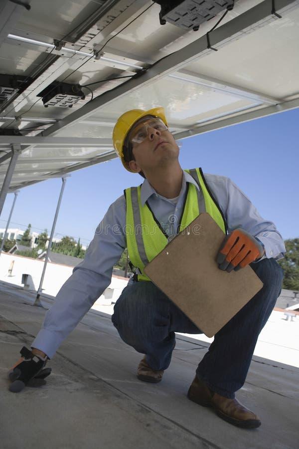Arbetare som kontrollerar solpaneler på tak royaltyfri bild