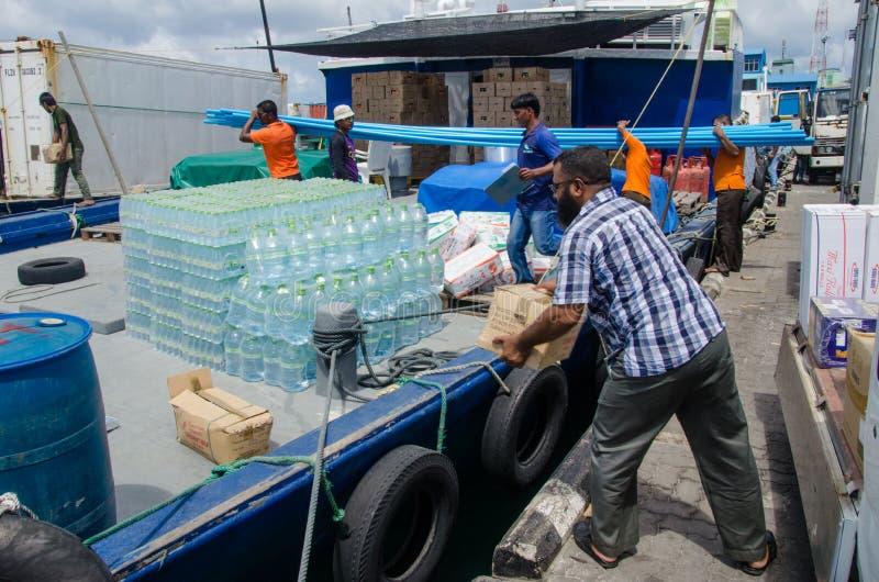 Arbetare som laddar gods i tillförselfartyg arkivbild
