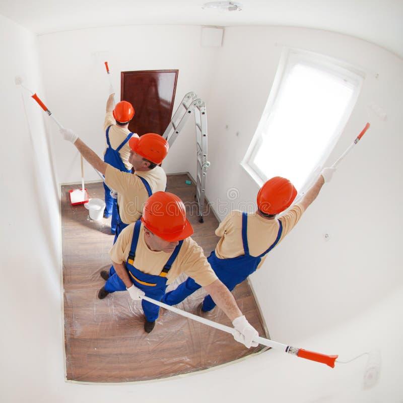 Arbetare som målar en vägg arkivbild