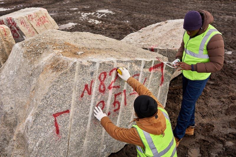 Arbetare som markerar Granit fotografering för bildbyråer