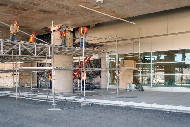 Arbetare som monterar materialet till byggnadsst?llning i en parkeringsplats under konstruktion arkivbilder