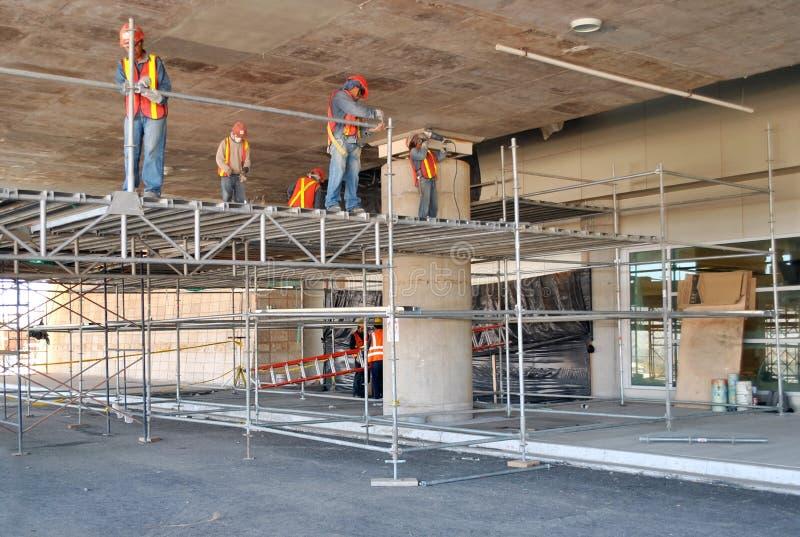 Arbetare som monterar materialet till byggnadsst?llning och arbetar p? taket av en parkeringsplats under konstruktion royaltyfri bild