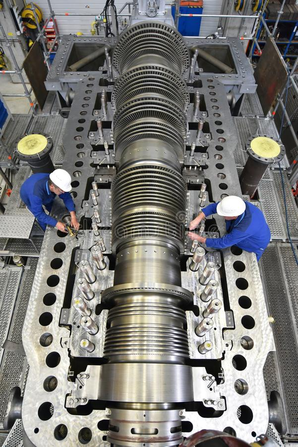 Arbetare som monterar, och kvalitets- kontroll av gasturbiner i ett funktionsläge royaltyfri bild