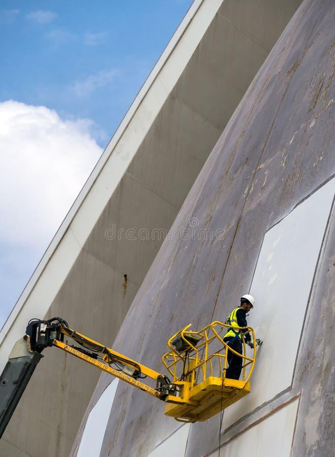 Arbetare som reparerar modern byggnad royaltyfria bilder