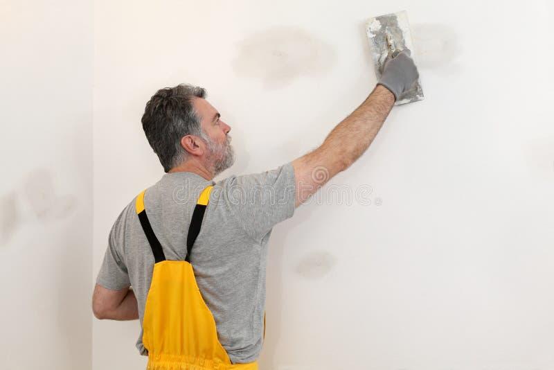 Arbetare som reparerar murbruk på väggen royaltyfri bild