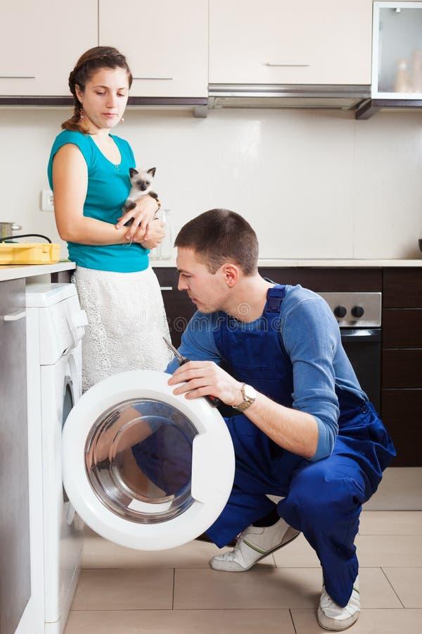 Arbetare som reparerar tvagningmaskinen royaltyfria bilder