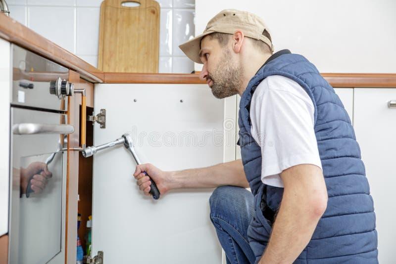 Arbetare som reparerar vasken i köket arkivfoto