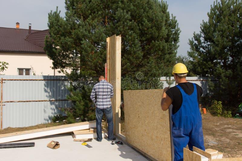 Arbetare som reser upp väggisoleringspaneler arkivfoton