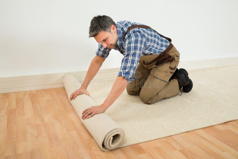 Arbetare som rullar ut matta på golv arkivbild