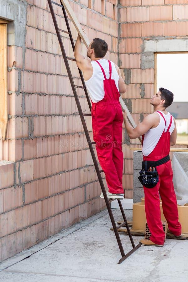 Arbetare som rymmer träbalken arkivfoto