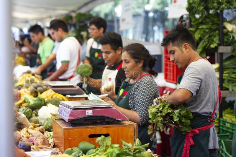 Arbetare som säljer grönsaker på gatamarknaden royaltyfri fotografi