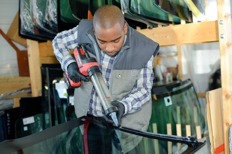Arbetare som sätter lim på exponeringsglas royaltyfria foton