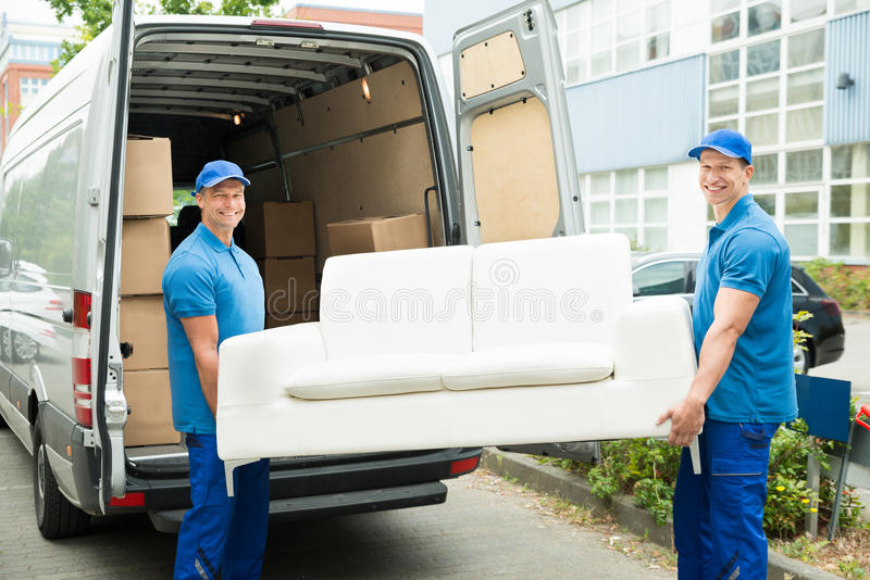 Arbetare som sätter möblemang och askar i lastbil royaltyfri bild