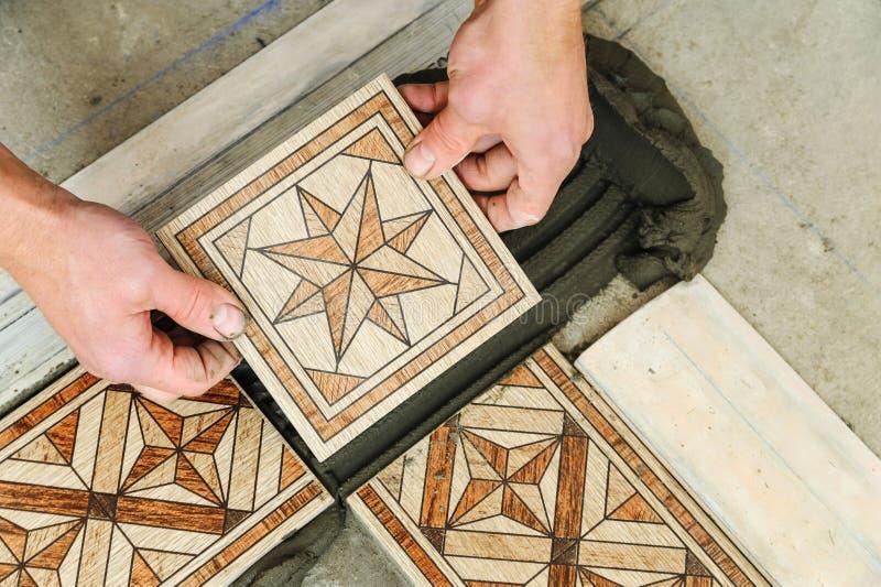 Arbetare som sätter tegelplattor på golvet arkivfoton